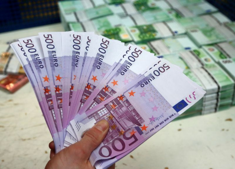FILE PHOTO: An employee holds 500 euro banknotes in the Money Service Austria company's headquarters in Vienna