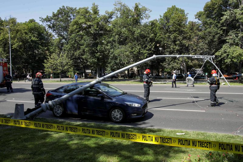 Firefighters and police officers inspect two fallen street lights following an emergency landing of US military Black Hawk helicopter