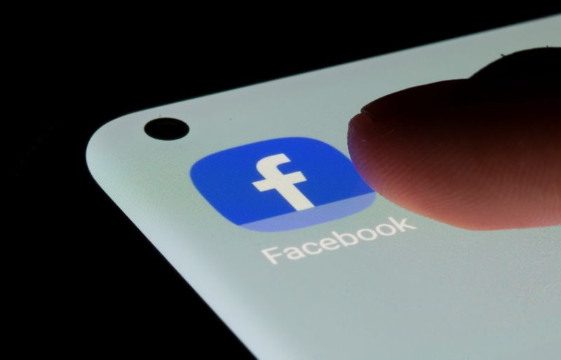 Facebook app is seen on a smartphone in this illustration