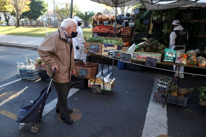 FILE PHOTO: A customer walks outside a shop at a greengrocery store in a street market, in Buenos Aires