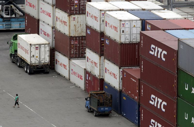 FILE PHOTO: A person walks near containers at Keelung port, northern Taiwan