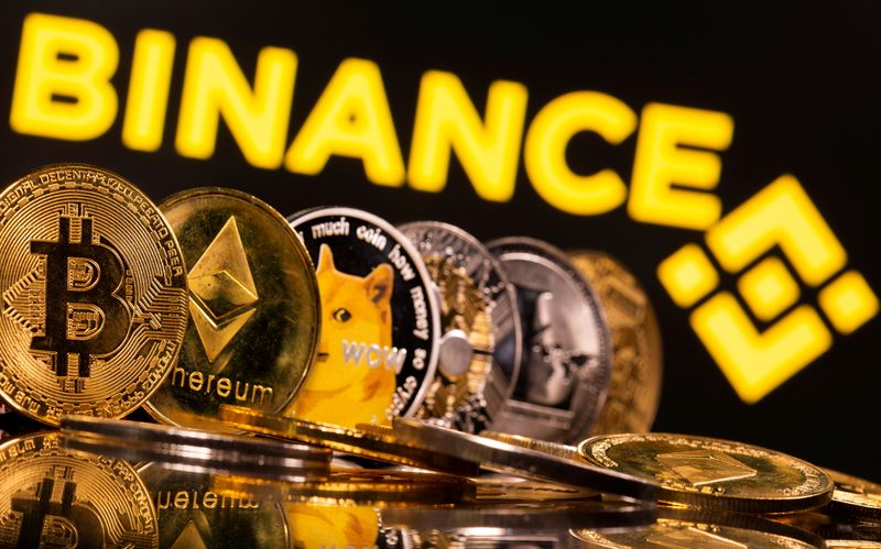 FILE PHOTO: Representations of cryptocurrencies Bitcoin, Ethereum, DogeCoin, Ripple, and Litecoin are seen in front of a displayed Binance logo