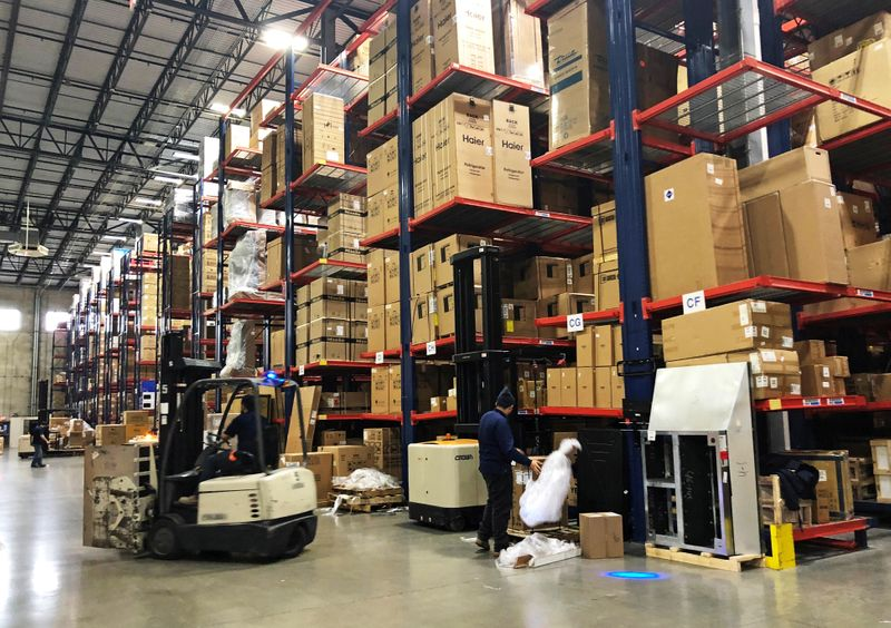Warehouse workers deal with inventory stacked up to the ceiling at an ABT Electronics Facility in Glenview