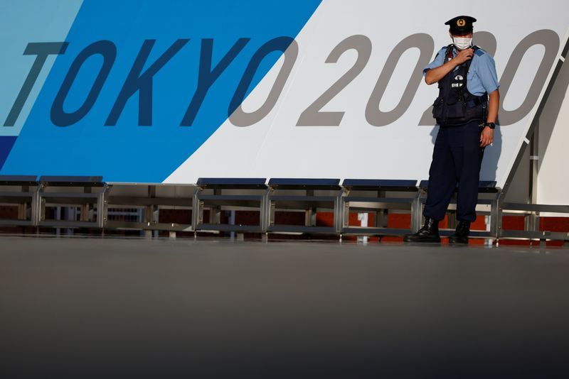 A police officer wearing a face mask stands in front Tokyo 2020 Olympic Games signage at the Main Press Center in Tokyo