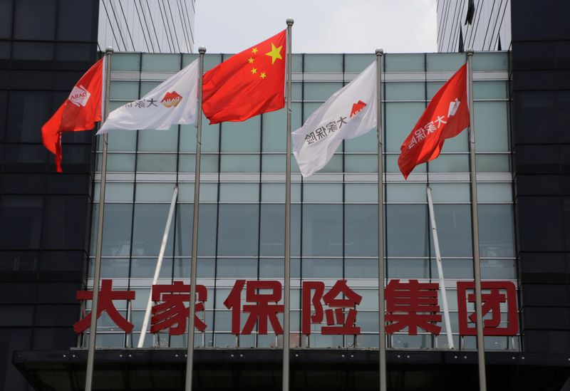 Company flags and the sign of Dajia Insurance Group are seen at the former headquarters of Anbang Insurance Group, in Beijing