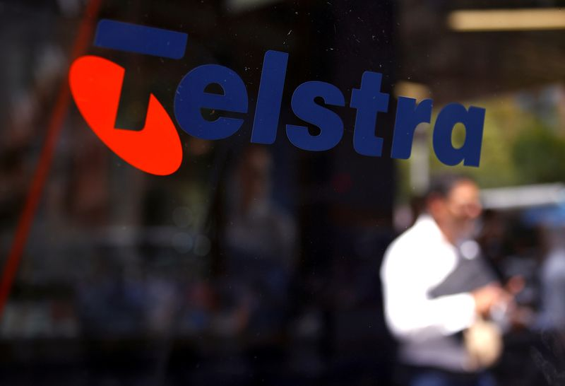 FILE PHOTO: A man looks at his phone as he walks past a Telstra logo adorning a phone booth in the central business district of Sydney