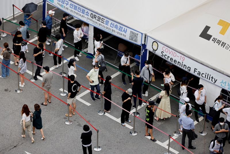 FILE PHOTO: People wait in line for a coronavirus disease (COVID-19) test at a testing site which is temporarily set up at a public health center in Seoul