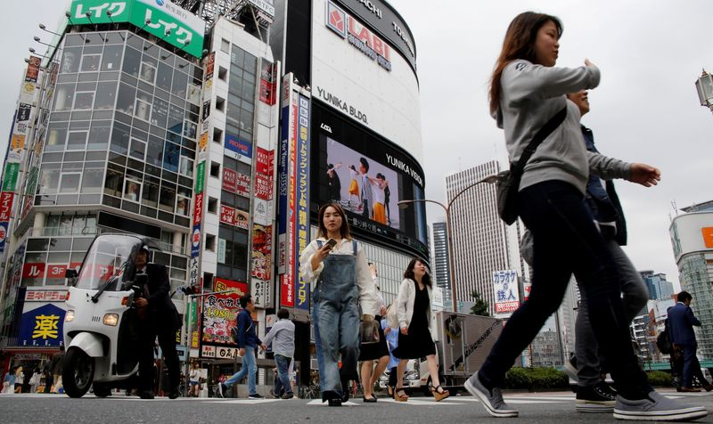 FILE PHOTO: People cross a street in the Shinjuku shopping and business district in Tokyo