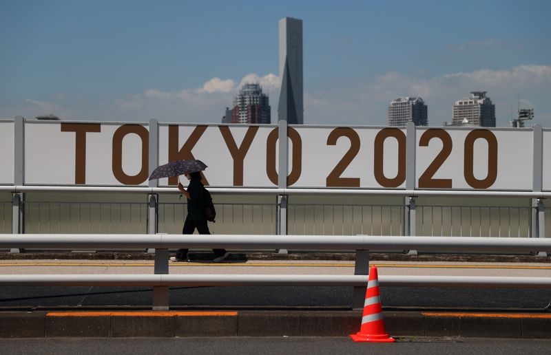 A woman shelters from the sun under an umbrella as she walks past Olympics signage