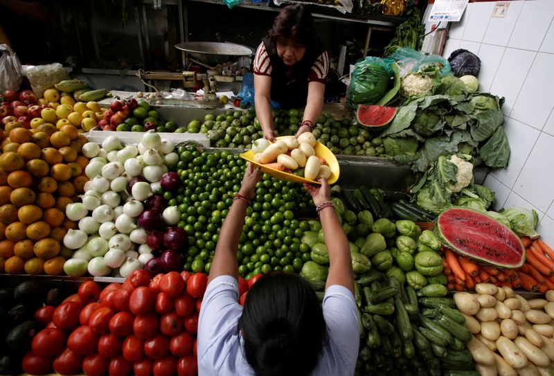 FILE PHOTO: A woman buys vegetables at a market stall in Mexico City