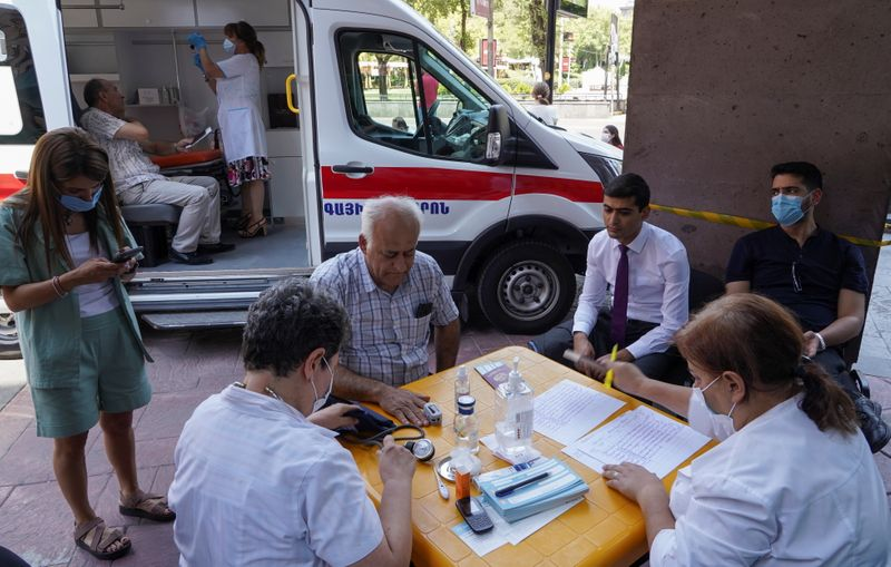 Iranian citizens prepare to get vaccinated against the coronavirus disease (COVID-19) at a mobile vaccination centre in Yerevan