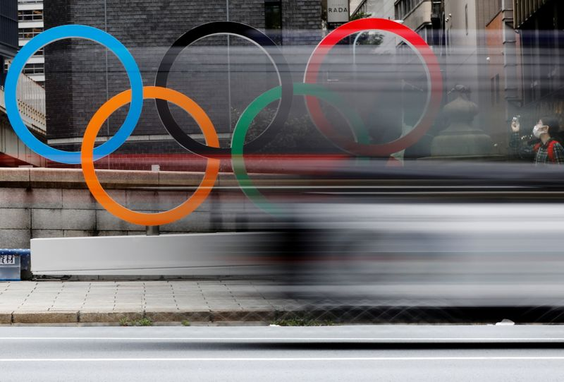 FILE PHOTO: A woman wearing a protective mask takes a photo of Olympic Ring promoting Tokyo 2020 Olympic Games in Tokyo, Japan, July 12, 2021.