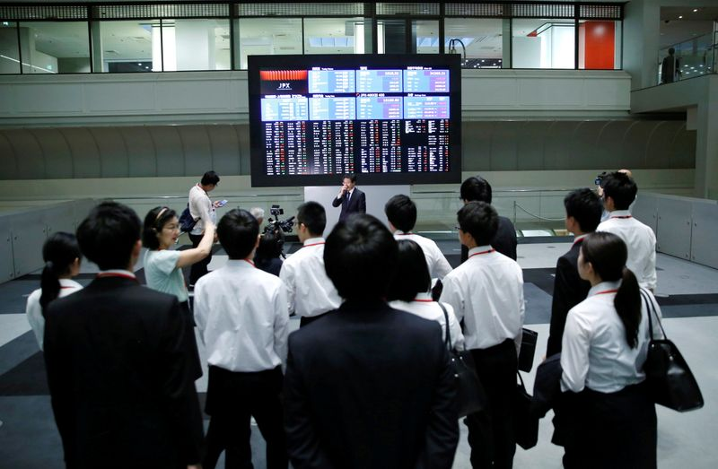 FILE PHOTO: Visitors look at an electronic stock quotation board at the TSE in Tokyo