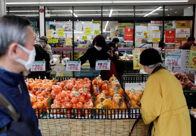 FILE PHOTO: Shoppers wearing protective face masks, following an outbreak of the coronavirus disease, are seen at a supermarket in Tokyo, Japan