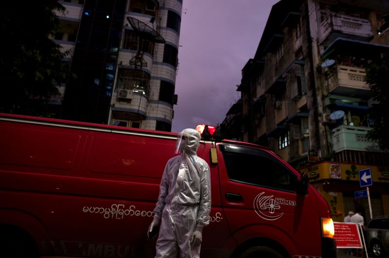 FILE PHOTO: FILE PHOTO: A medical staff wearing a protective suit stands near an ambulance, amid the outbreak of the coronavirus disease (COVID-19), in Yangon