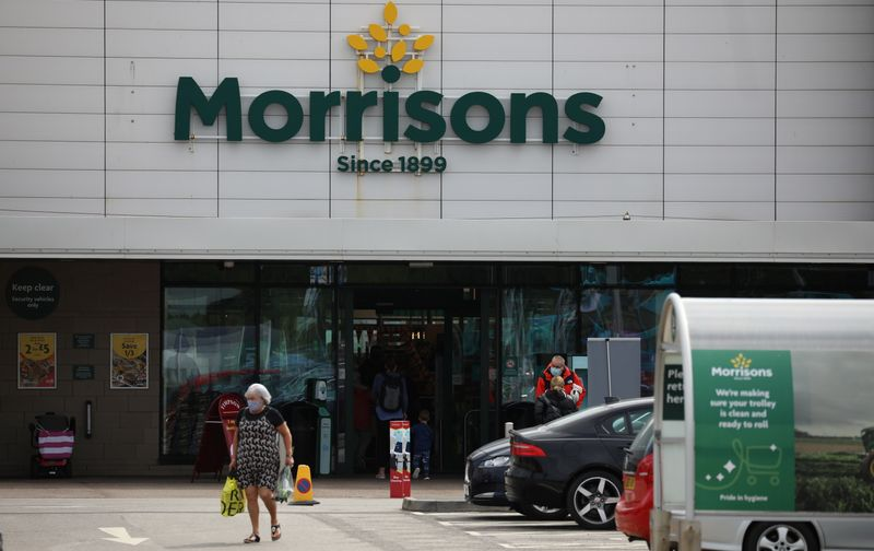 A customer carries a shopping bag outside a Morrisons supermarket in New Brighton