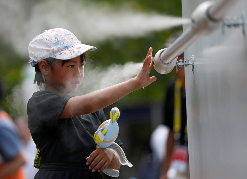 FILE PHOTO: A visitor experiences a large-scale misting tower dispensing ultra-fine mist during a proving test of heat countermeasures for the Tokyo 2020 Olympic and Paralympic Games in Tokyo