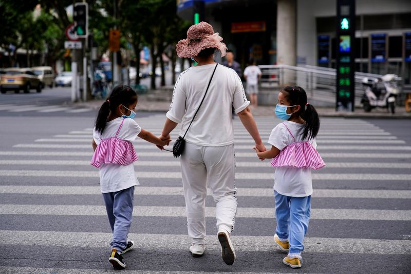 A mother walks with her twin daughters on a street in Shanghai