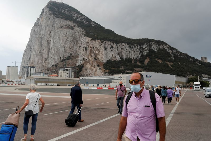 FILE PHOTO: People cross the tarmac of the airport in front of the Rock of Gibraltar in the British overseas territory of Gibraltar