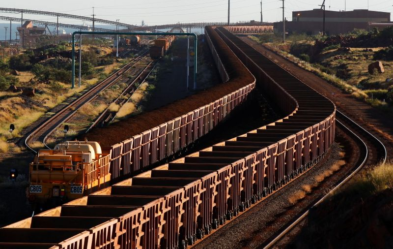 FILE PHOTO: A train loaded with iron ore travels towards the Rio Tinto Parker Point iron ore facility as an empty train leaves in Dampier