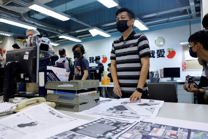 FILE PHOTO: Staff members of Apple Daily work on their final edition in Hong Kong