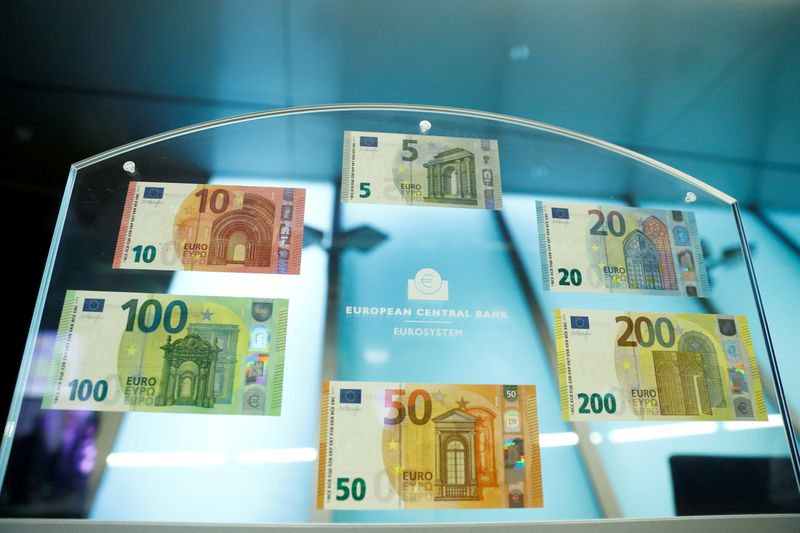FILE PHOTO: FILE PHOTO: People hold new 100- and 200-euro banknotes during a presentation at the ECB headquarters in Frankfurt,