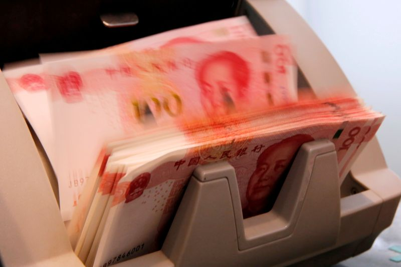 FILE PHOTO: Chinese 100 yuan banknotes are seen in a counting machine while a clerk counts them at a branch of a commercial bank in Beijing