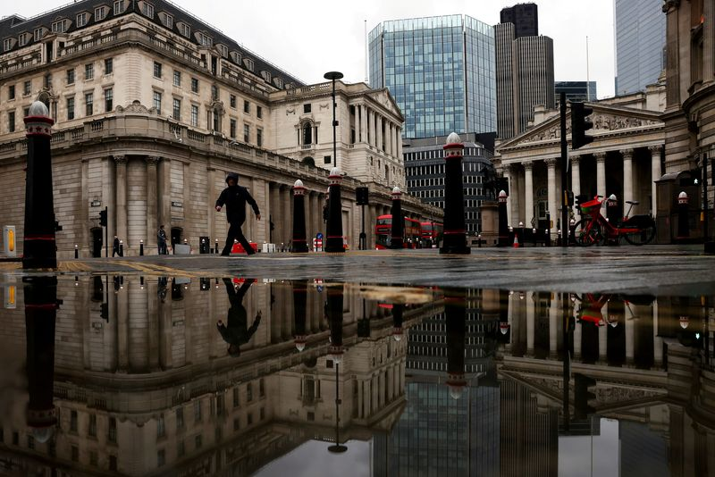 FILE PHOTO: The Bank of England and Royal Exchange are reflected in a puddle as a pedestrian walks past in London