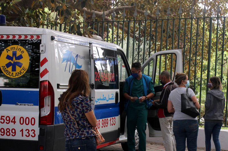 FILE PHOTO: People wait to get tested for COVID-19 outside a mobile testing lab in Tunis
