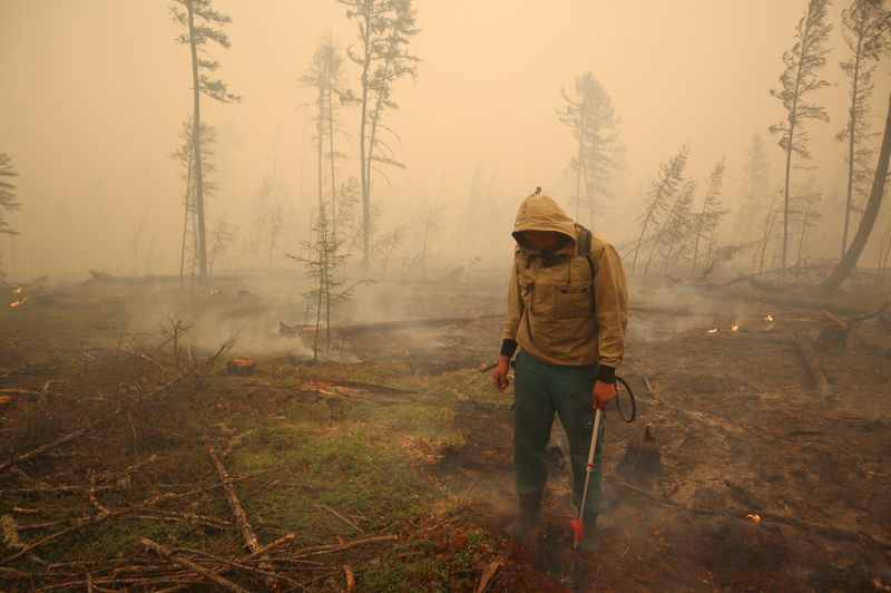 FILE PHOTO: A specialist of the local forest protection service works to extinguish a forest fire near the village of Magaras in the region of Yakutia, Russia July 17, 2021