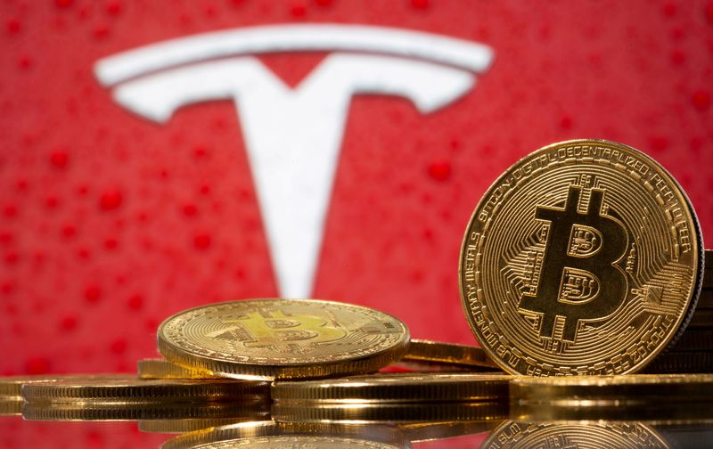 FILE PHOTO: Representations of virtual currency bitcoin are seen in front of Tesla logo in this illustration