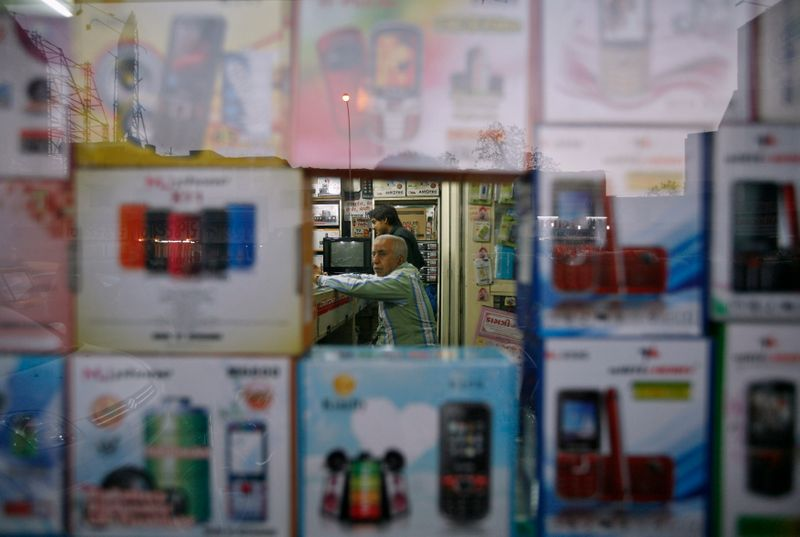 A vendor waits for customers inside his shop that sells mobile phones at Surat, in the western Indian state of Gujarat