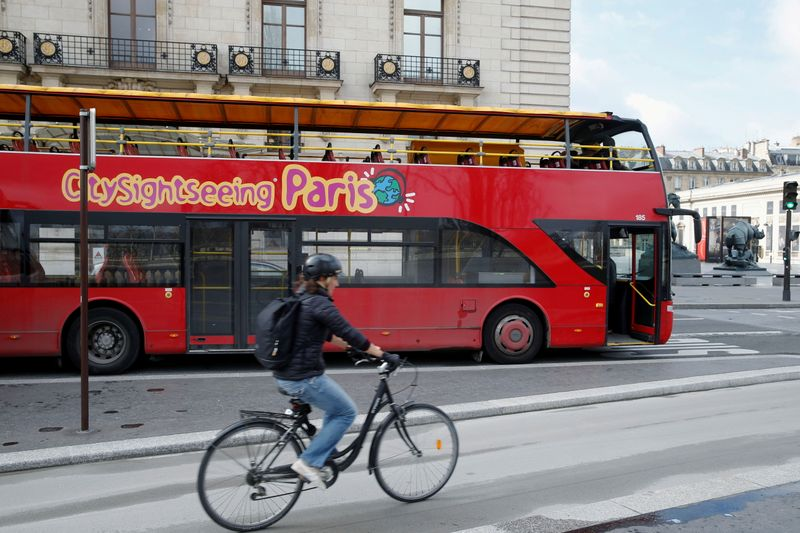 FILE PHOTO: A cyclist rides past an empty tourist bus on the street of Paris