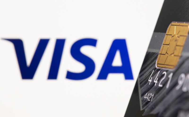 Credit card is seen in front of displayed Visa logo in this illustration