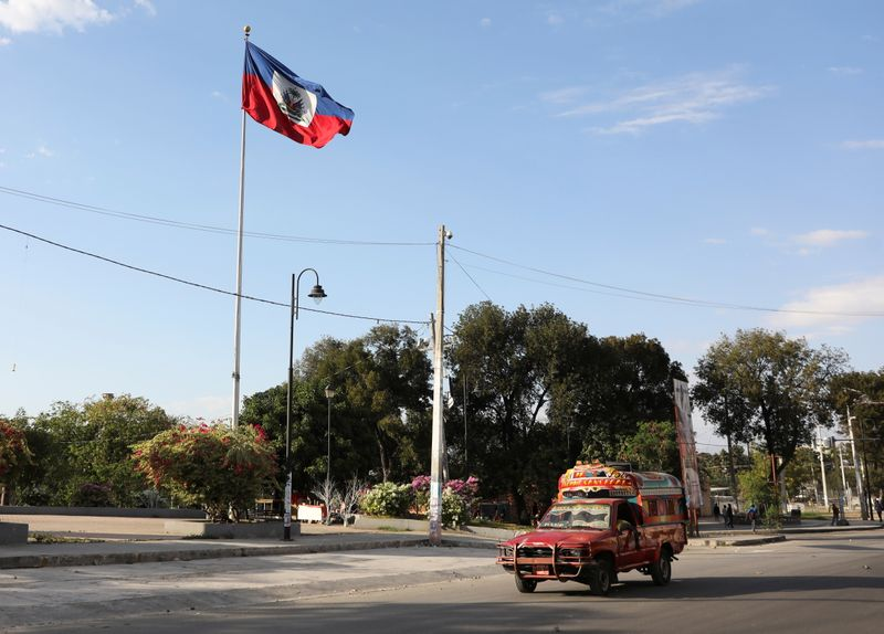 A Tap-Tap (a collective transportation vehicle) drives past the national flag, in Port-au-Prince, Haiti