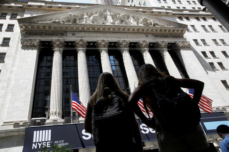 Members of a tour group look at the front facade of the NYSE in New York