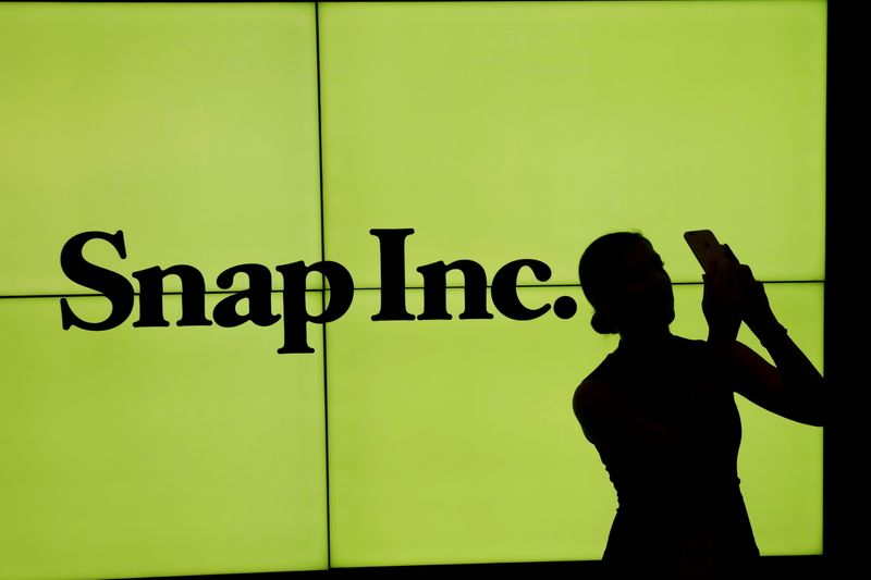 FILE PHOTO: A woman stands in front of the logo of Snap Inc on the floor of the New York Stock Exchange (NYSE) in New York City