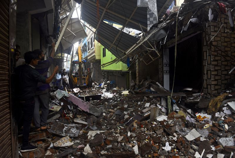 People use their mobile phones to take pictures of a collapsed building following rains in Mumbai