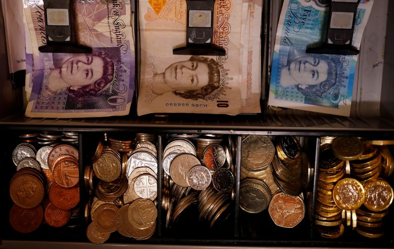 FILE PHOTO: Pound notes and coins are seen inside a cash register in a bar in Manchester, Britain