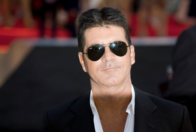 FILE PHOTO: Television mogul Simon Cowell poses for photographers as he arrives for the film