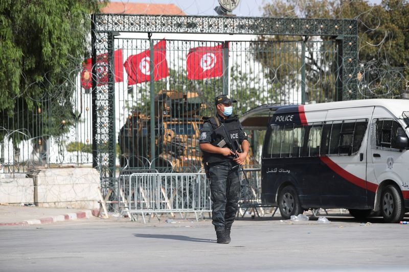 Police officers stand guard outside the parliament building in Tunis