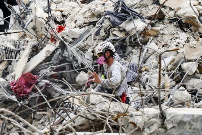 A search and recovery team member moves through the rubble of the Champlain Towers South condo in Surfside, Fla. (AP Photo via Al Diaz/Miami Herald)