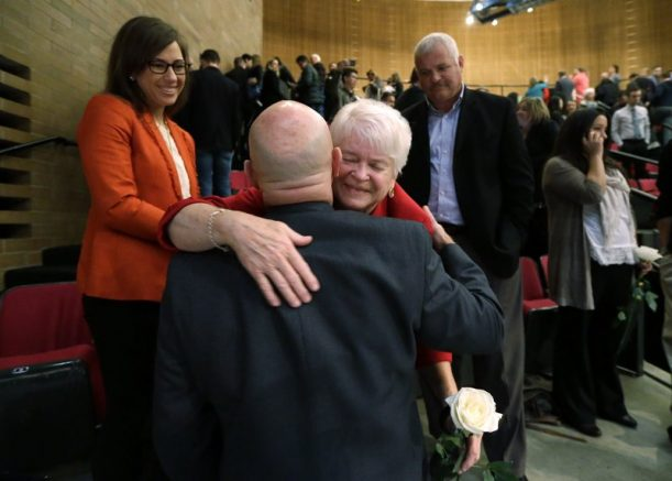 Barronelle Stutzman, center, a florist who was fined for denying service to a gay couple in 2013, holds a flower as she embraces a supporter after a hearing before Washington's Supreme Court in Bellevue, Wash. (AP Photo/Elaine Thompson)