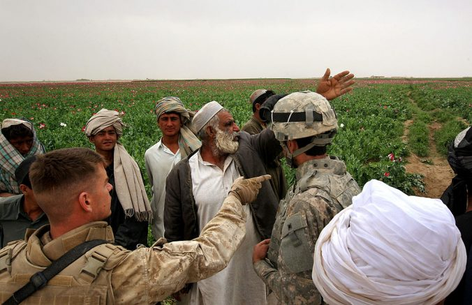 QALANDERABAD, AFGHANISTAN - MARCH 22: Opium farmer Haji Abdul Khan shows off damaged poppies to U.S. Marines and their military interpreter on March 22, 2009 near remote Qalanderabad in southwest Afghanistan. The opium poppy field was damaged when a U.S. Air Force airdrop of supplies blew off target, parachuting on to some of Khan's crops and crushing them. The Marines assured Khan they would pay him for his damaged poppy crop in compensation for the accident. The Taliban often extorts a percentage of the profits from the farmers' harvest to fund attacks on American forces, according to the military. U.S. Marines, however, have no mandate to destroy poppy crops and, in fact, count on farmers to supply intelligence on Taliban activities. (Photo by John Moore/Getty Images)