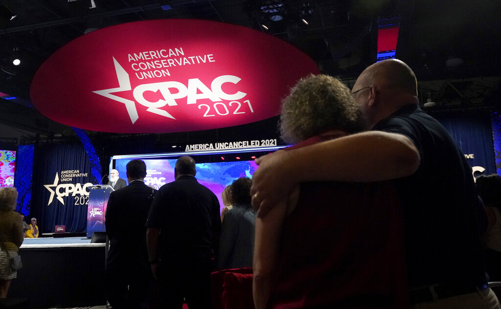 Conservative supporters look on as Rabbi Yitz Tender leads a prayer during the opening general session of the Conservative Political Action Conference (CPAC) Friday, July 9, 2021, in Dallas. (AP Photo/LM Otero)