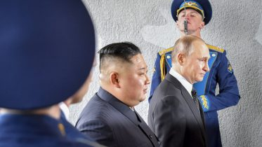 FILE - In this Thursday, April 25, 2019 file photo, President Vladimir Putin and North Korean leader Kim Jong Un, center, walk past honor guard officers during their meeting in Vladivostok, Russia. A plunging standard of living, a weak leader in Boris Yeltsin, thug businessmen and budding oligarchs fighting for control of state-owned businesses opened the way for Putin. (Yuri Kadobnov/Pool Photo via AP, File)