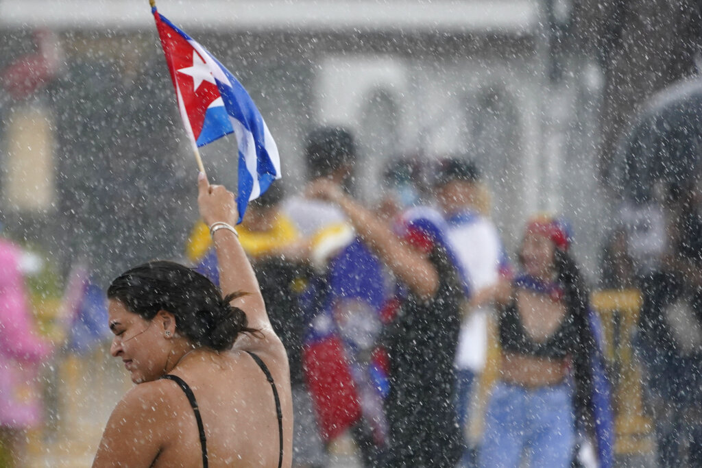 A demonstrator waves a Cuban flag in the rain, Wednesday, July 14, 2021, in Miami's Little Havana neighborhood, as people rallied in support of antigovernment demonstrations in Cuba. (AP Photo/Wilfredo Lee)