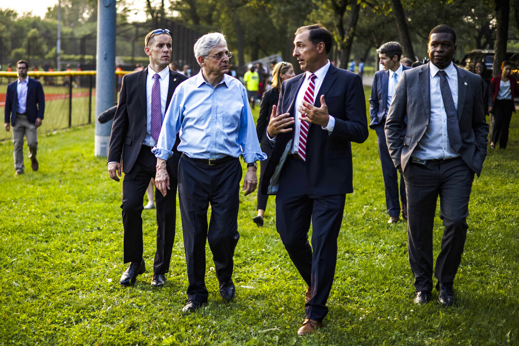 Attorney General Merrick Garland, center, talks with John Lausch, the U.S. Attorney for the Northen District of Illinois, as they walk between youth baseball game held by the Chicago Westside Sports, a part of The Chicago Police Department's formed Police Athletic League, at Columbus Park in Chicago, Illinois, Thursday, July 22, 2021. Garland is vowing that the Justice Department will crack down on gun trafficking corridors as part of a comprehensive approach to combat surging gun violence. (Samuel Corum/Pool via AP)