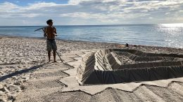 Sand sculptors adorns the beach beside the area that is closed for search and rescue operations at the partially collapsed Champlain Towers South condo building, Friday, July 2, 2021, in Surfside, Fla. (AP Photo/Terry Spencer)