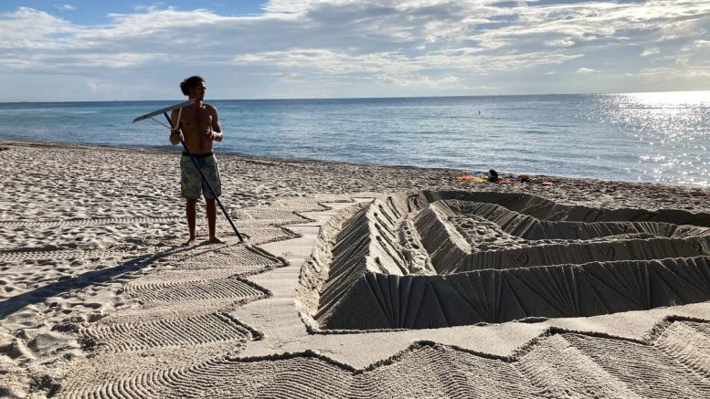 Sand sculptor adorns the beach beside the area that is closed for search and rescue operations at the partially collapsed Champlain Towers South condo building in Surfside, Fla. (AP Photo/Terry Spencer)